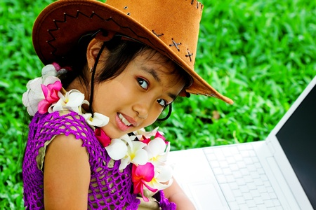 A girl wearing a cowboy hat with laptop in the garden photo