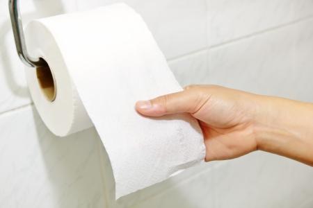 A mão da mulher segurando o rolo de papel higiênico