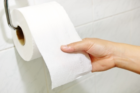 Woman hand holding the roll of toilet paper Stock Photo