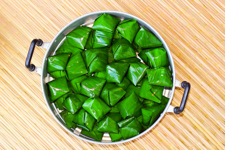 sticky hands: Thai desserts,wrap by banana leaf nature background