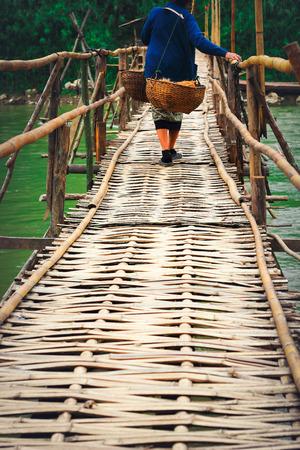 hawker: Hawker woman waking on bamboo bridge scene in Luang prabang,Laos