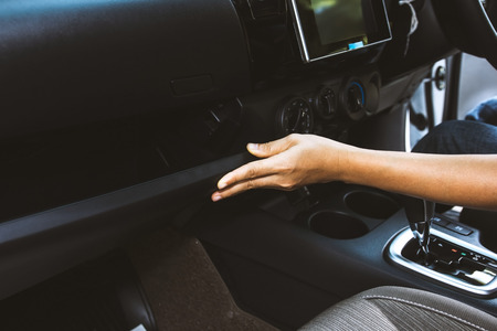 Woman hand opening glove compartment front panel in car