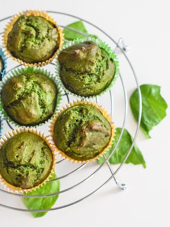 Freshly baked healthy spinach muffins on rack, healthy dessert, snack, flat lay top view, homemade muffins