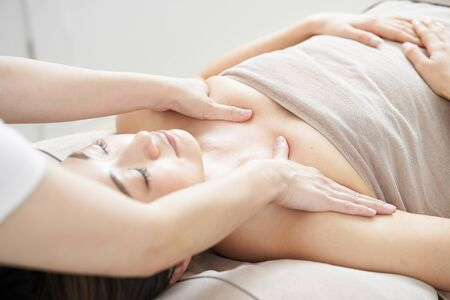 A woman gets a decollete massage at a bright beauty salon Stock Photo