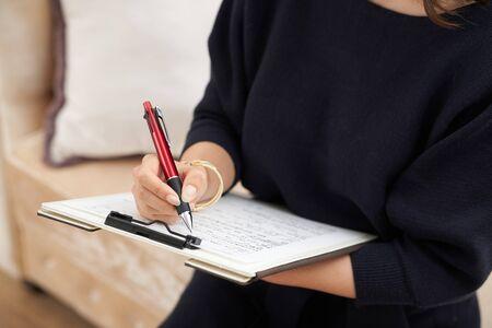 La main de la femme qui remplit les dossiers médicaux et les questionnaires Banque d'images