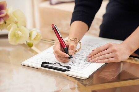 De hand van de vrouw die medische dossiers en vragenlijsten invult