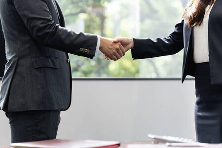 Händedruck zwischen einem männlichen Geschäftsmann und einer weiblichen Geschäftsfrau Standard-Bild