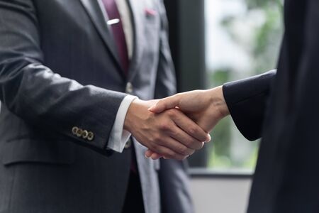 Handshake between a male businessman and a female businesswoman Stock Photo