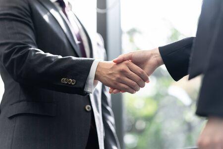 Handshake between a male businessman and a female businesswoman Standard-Bild - 134775168