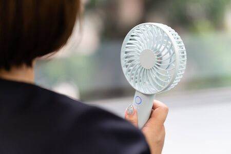 A woman uses portable fan