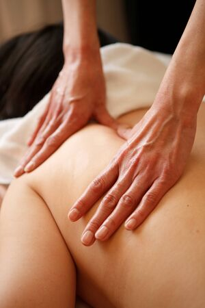 Estheticians hand sheds the lymph of the scapula in the beauty salon
