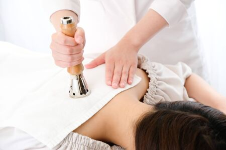 Acupuncturist who performs a womans back in a bright room with an MT type heater