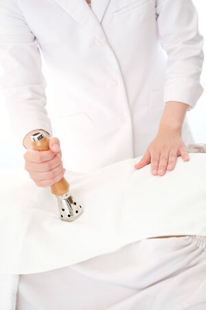 Acupuncturist who performs a woman's back in a bright room with an MT type heater