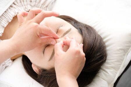 The hand up of the woman and the practitioner who is struck by acupuncture in the face in the acupuncture clinic