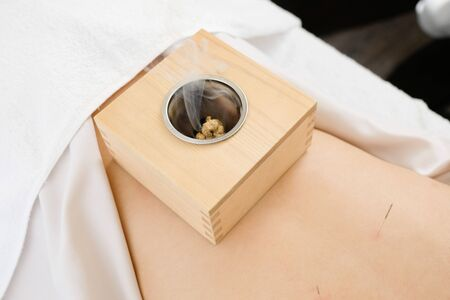 A box bowl placed on a womans waist in a bright acupuncture clinic