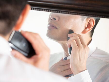 a male businessman who shaves in a hurry while looking in the mirror Banque d'images