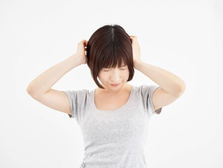 A woman holding her aching head in a white background