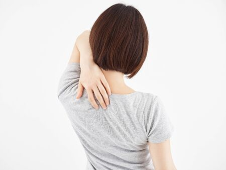 A woman holding the scapula hurting in a white background