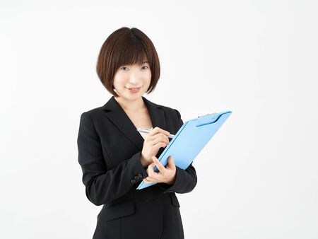Woman OL taking notes on binder with a smile on a white background