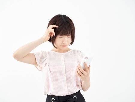 A woman who operates a smartphone while holding her head