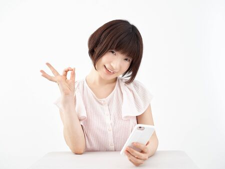 A woman who sits and gives an OK sign while holding a smartphone