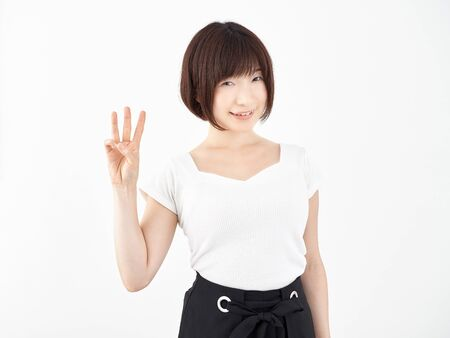 a woman posing 3 with her fingers on a white background