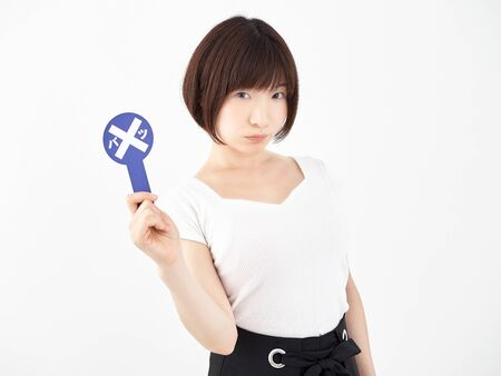 grumpy woman with a pinsign on a white background 写真素材
