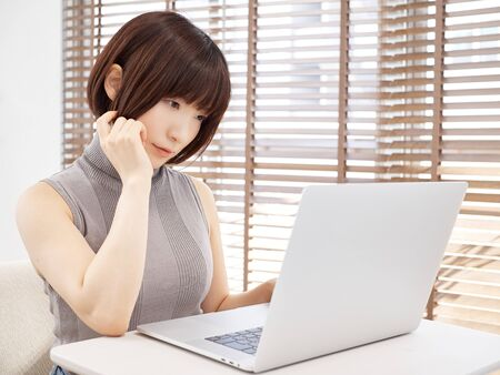 A woman who operates a personal computer while worrying in a bright living room 写真素材