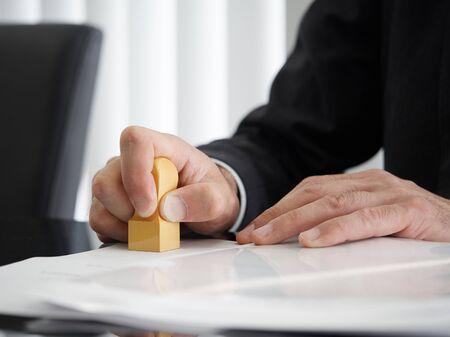de hand van een gerechtsdeurwaarder met een vierkant merkteken