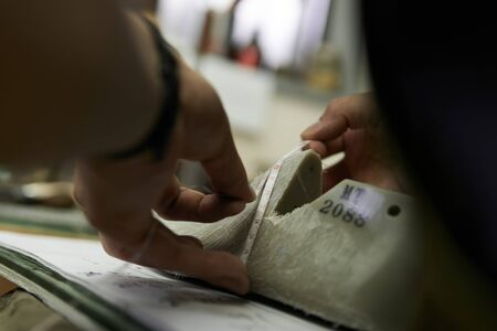 the hand of a shoemaker measuring the mold of leather shoes