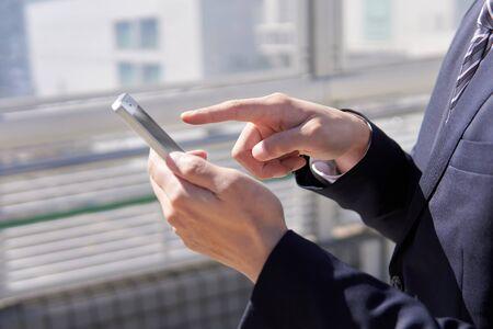 Japanese male businessman who operates smartphone