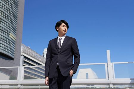 Japanese male businessman standing in the office district Banco de Imagens