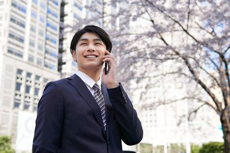 Japanese male businessman who calls with a smartphone against the background of cherry blossoms in the office district Stok Fotoğraf