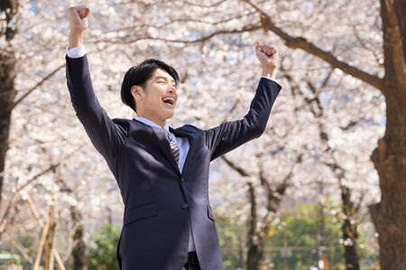 Japanese male businessman posing in a gutsy pose against the background of cherry blossoms Stok Fotoğraf