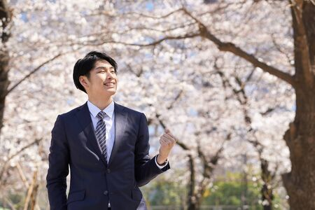 Japanese male businessman posing in a gutsy pose against the background of cherry blossoms Banco de Imagens