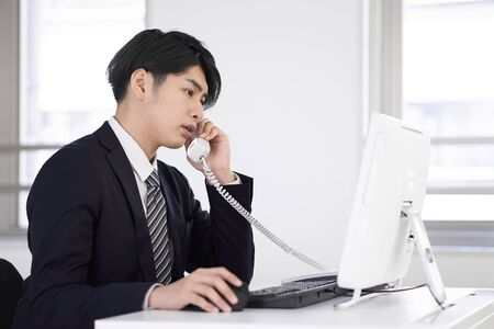 Japanese male businessman answering on the phone