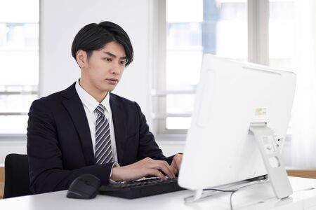 Japanese male businessman who does pc work with a serious expression 写真素材