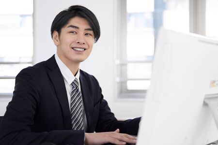 Japanese male businessman who works on a personal computer with a smile