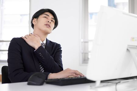 Japanese male businessman suffering from stiff shoulders