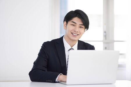 Japanese male businessman who wears a suit and teleworks at home with a smile 写真素材