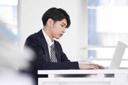Japanese male businessman who concentrates and works on a laptop