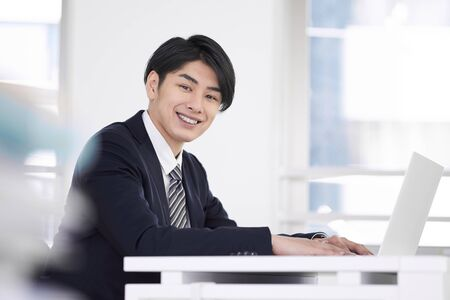 Japanese male businessman working with a laptop with a smile