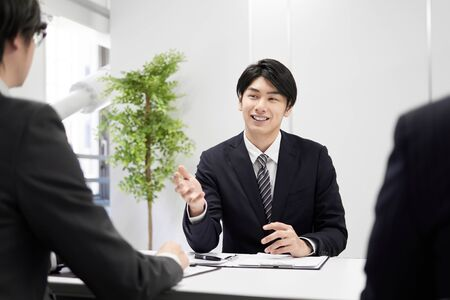Japanese male businessman explaining face-to-face