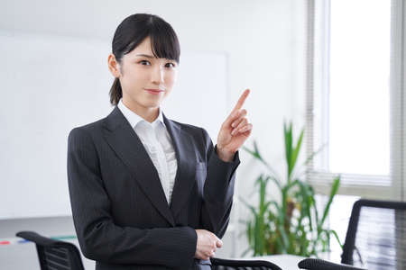 Japanese female businesswoman explaining by pointing at the office