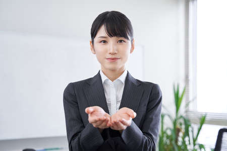 Japanese woman businesswoman holding out her hands in the office