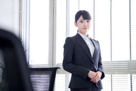 Japanese woman businesswoman standing by the window of the office