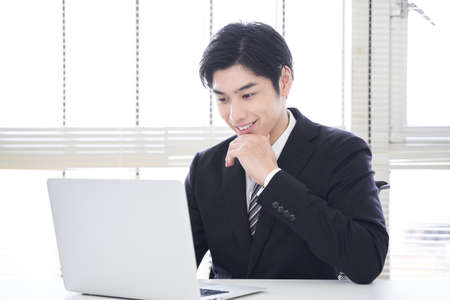 Japanese male businessman working with a smile on his laptop in the office