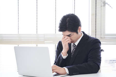 Japanese male businessman fails to operate laptop in office Stock fotó