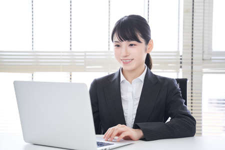Japanese woman businesswoman who operates a laptop with a smile in the office