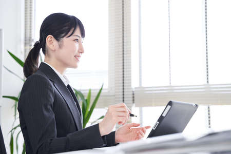Japanese female businesswoman hearing using a tablet in the office Archivio Fotografico